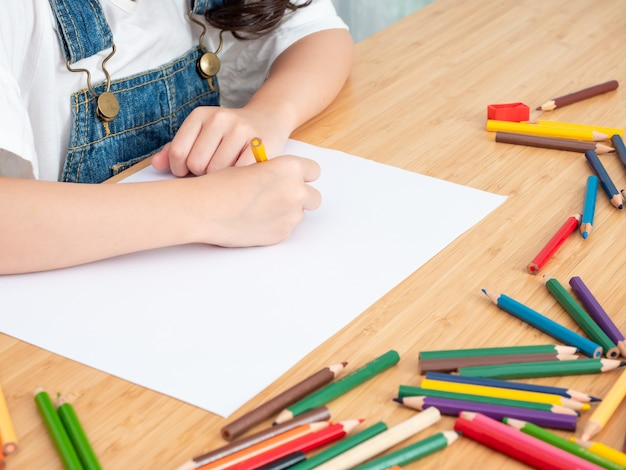 Close up hand of little cute girl use colors pencil drawing at white paper on wooden table.