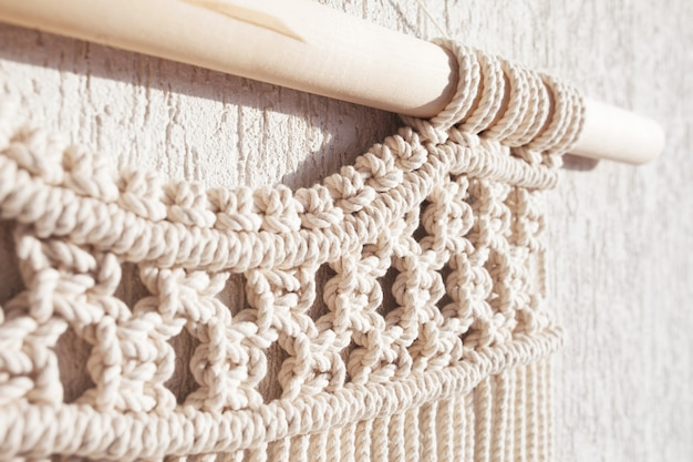 Close-up of hand made macrame texture pattern. eco friendly modern knitting diy natural decoration concept  in the interior.  handmade macrame 100% cotton. female hobby.