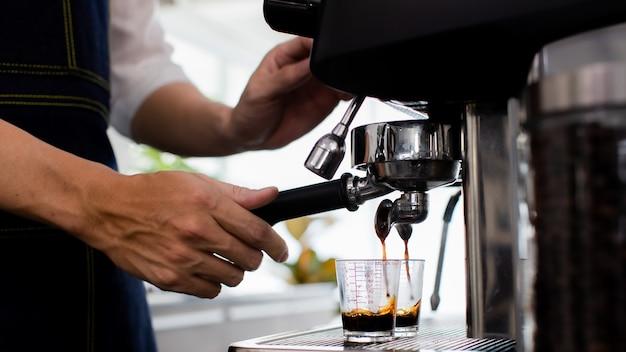 Закройте руку. приготовление чашки кофе в кофеварке, пара и чашка. машина для приготовления эспрессо с портафильтром заделывают. концепция кофеварка в кафе.