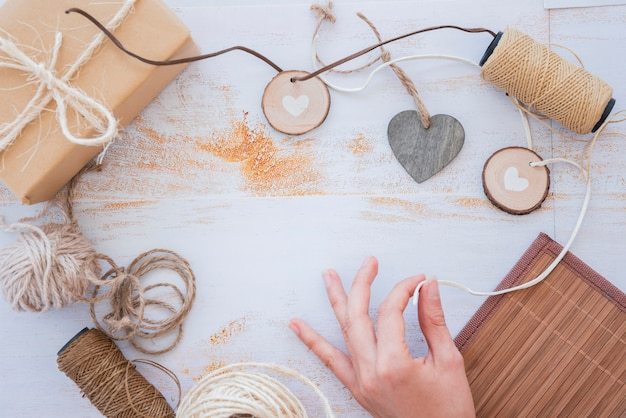 Close-up of hand making heart garland with spool and wrapped gift box on white desk