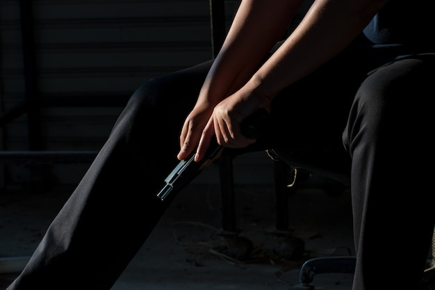 Close up hand of a man carrying a gun with bullet in the chamber