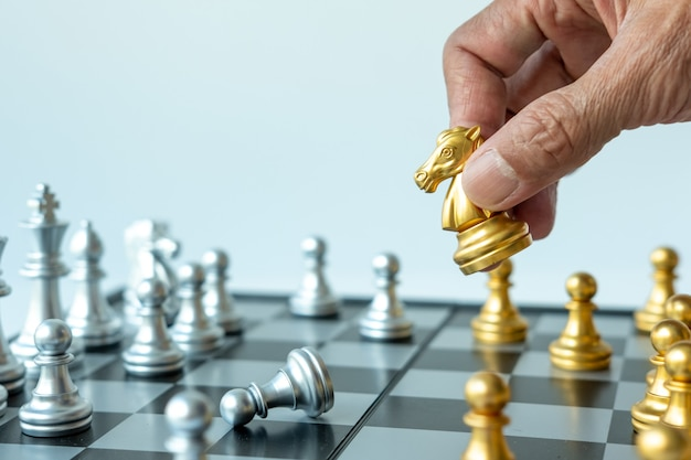 Close up of hand of man holding gold chess horse on chess board , copy space for your text.