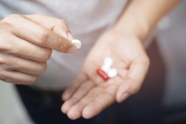 Закройте вверх по руке человека, держащего несколько таблеток. прекратить употребление наркотиков принимать лекарства медицинской концепции здравоохранения.