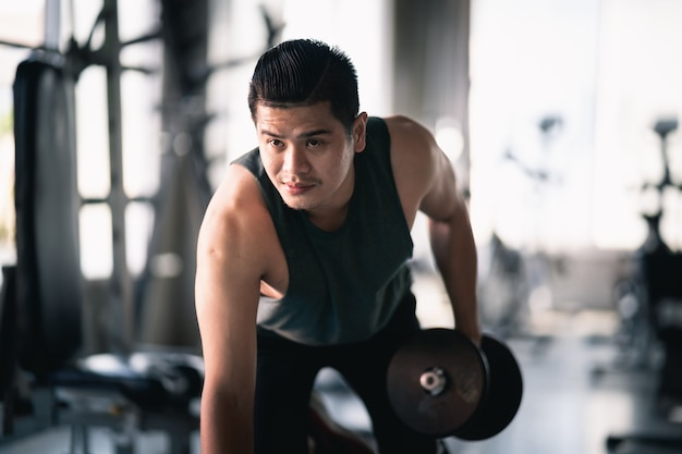 Close up of hand man using dumbbell exercise at gym, sport concept