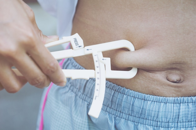 Close-up of hand measuring his body fat of sporty woman