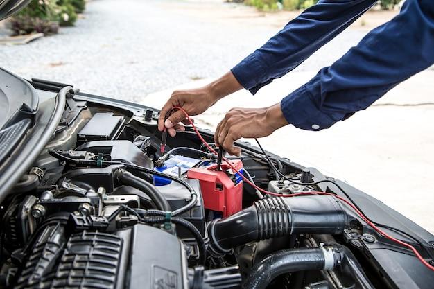 자동차 배터리를 확인하는 측정 장비를 사용하여 손 정비사를 닫습니다.
