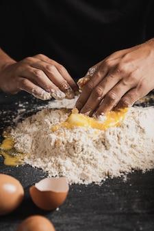 小麦粉と卵黄を混合するクローズアップ手