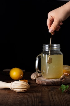 Close-up hand mixing jar filled with homemade lemonade