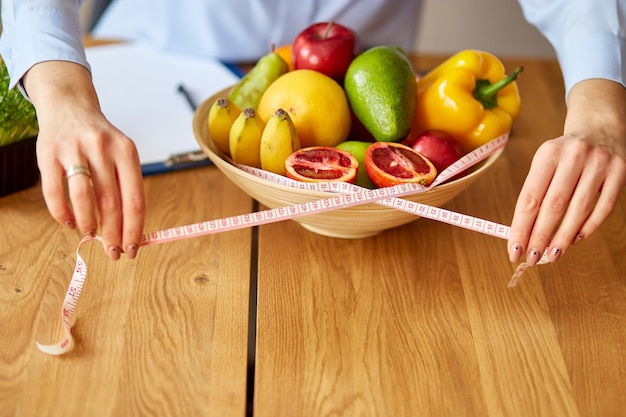 Close up of hand nutritionist, dietitian workplace, woman hold measuring tape and measuring bowl with healthy vegetables and fruits, healthcare and diet, right nutrition and slimming wellness concept.