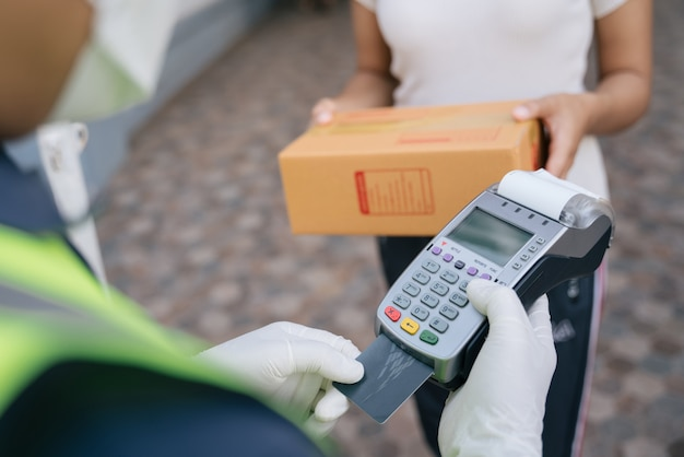 Закройте руку курьера, использующего устройство для чтения кредитных карт, при доставке продуктов клиентам на дом, место доставки.