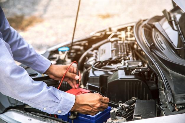 자동차 배터리 측정을 사용하여 자동차 정비사의 손을 닫습니다.