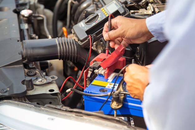 Закройте вверх по руке автомеханика, используя измерительный инструмент, проверяющий аккумулятор автомобиля.