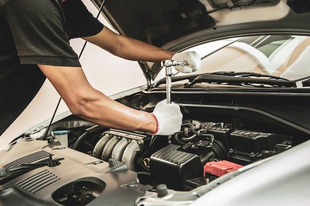 Крупным планом рука автомеханика с помощью гаечного ключа для ремонта двигателя автомобиля.