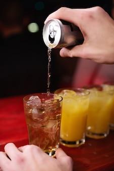 バーテンダーのクローズアップの手は、ナイトクラブでオレンジジュースとアルコールカクテルにエネルギードリンクを注ぐ