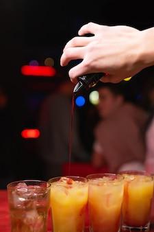 バーテンダーのクローズアップの手がナイトクラブでオレンジジュースとアルコールカクテルにシロップを注ぐ