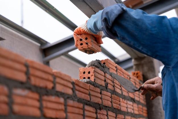 건설 현장에서 외벽에 벽돌 벽돌을 설치하는 벽돌공 작업자의 손을 닫습니다