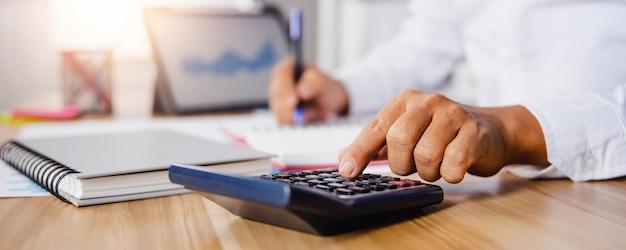 金融収入と利益をチェックするために計算機を押すビジネスマンの手をクローズアップ