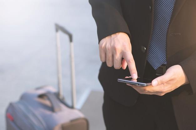 デバイスを保持し、画面に触れるテキスト モバイル スマート フォンを使用してビジネスの男性の手を閉じます。またはお客様にお問い合わせください。