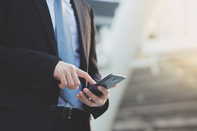 텍스트 모바일 스마트 전화 장치를 들고 화면을 터치를 사용 하여 비즈니스 남자의 손을 닫습니다. 또는 고객에게 문의하십시오.