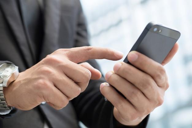 デバイスを保持しているテキスト モバイル スマート フォンを使用してビジネスの男性の手を閉じる