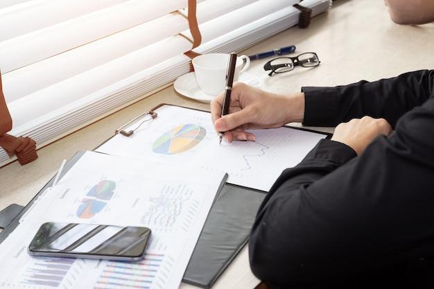 Закройте вверх руку делового человека, работающего с финансовыми данными