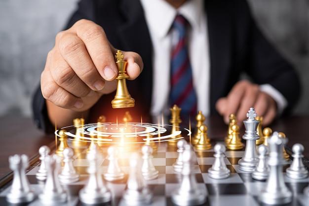 Закройте вверх по руке бизнесмена, держащего шахматную фигуру