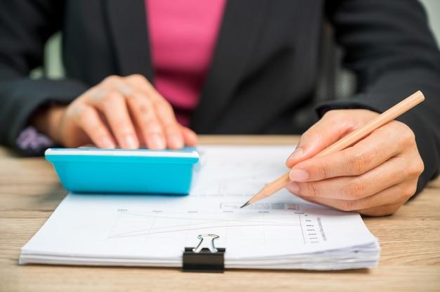 計算機の家計または機械の税金、財務および会計の概念を使用して、実業家の手をクローズアップします。