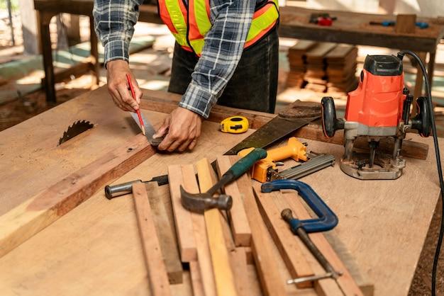 Закройте вверх по руке плотника, работающего на деревообрабатывающих станках в столярной мастерской. плотник работает на строительной площадке