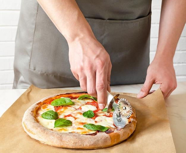 キッチンで灰色の均一なカッティングピザのシェフのパン屋の手をクローズアップ