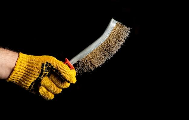 Крупным планом рука мастера в перчатке держит кисть для удаления ржавчины