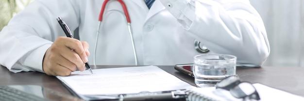 Закройте вверх руки врача, профессии болезни, пишущей симптомы болезни после исследования и лечения пациента на столе