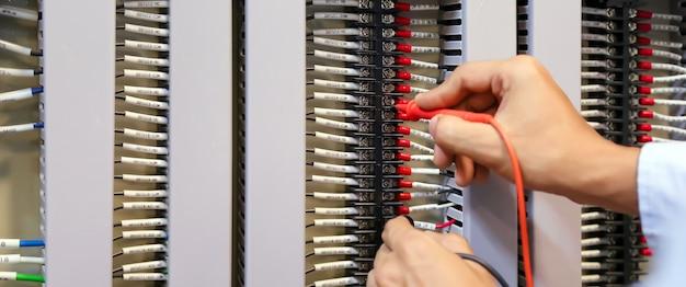 電気のチェックに測定を使用して電気工学のクローズアップの手。