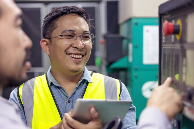 工場でタブレットを使用して電気システムをチェックする作業をしているエンジニアまたは電気技師の手をクローズアップします。