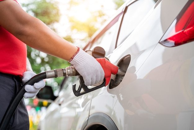 Крупным планом рука работника заправки газа в перчатках заправляет клиентов, перекачивая газ оборудования на азс.