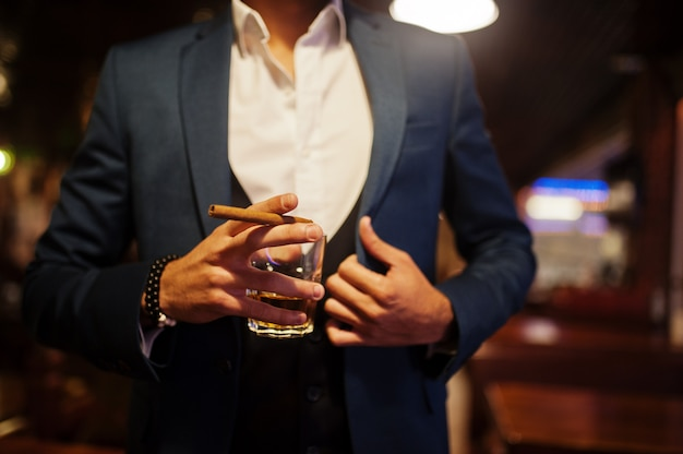 パブでポーズをとってウィスキーと葉巻のグラスとハンサムな身なりのアラビア人の手を閉じます。