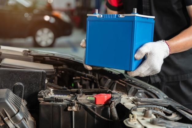 자동차 서비스 센터에서 자동차 배터리를 교체하는 남성 정비사의 손을 가까이, 컨셉트 자동차 유지 보수