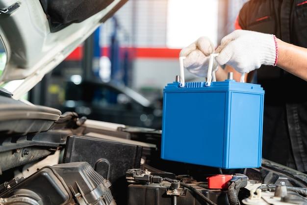 자동차 배터리를 교체하는 남성 정비사의 손을 닫고 엔지니어는 자동차 서비스 센터에서 자동차 배터리가 고갈되었기 때문에 자동차 배터리를 교체하고 있습니다.