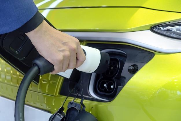흰색 전기 자동차의 소켓에 충전기 배터리 용 충전식 기계 플러그를 들고 남자의 근접 손