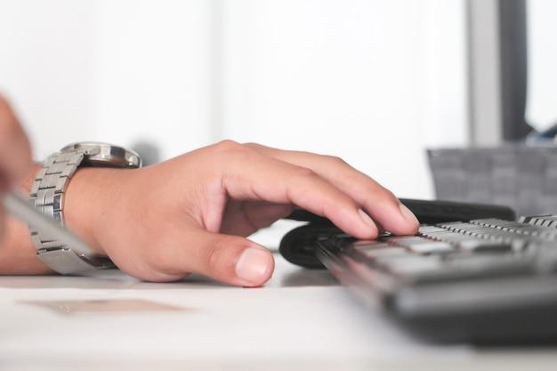 キーボードと古いsrceenディスプレイで男の手を閉じます。ワーキングオフィスのコンセプト。忙しくて真面目なコンセプトの作品。サラリーマンの概念。