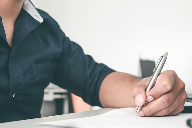 オフィスで紙にペンを書く男の手を閉じます。ワーキングオフィスのコンセプト。仕事のコンセプト。サラリーマン。アカウントまたは財務概念。