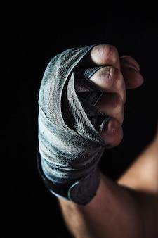 包帯で筋肉質の男のクローズアップ手