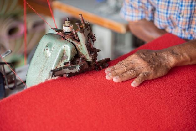 赤い敷物を縫う老人の手をクローズアップ