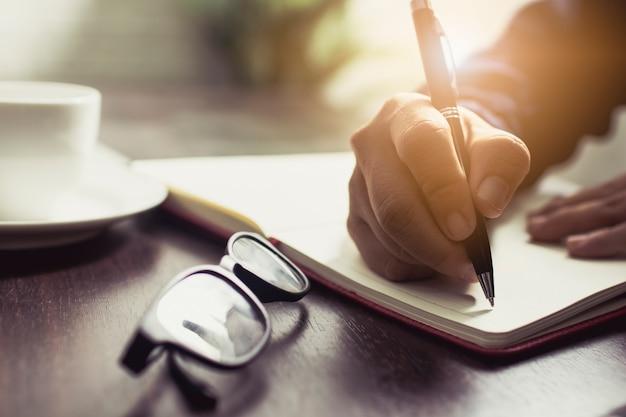 집에서 작업 테이블에 진 쓰기 일기와 메모 정보를 착용하는 사람들의 손을 닫습니다