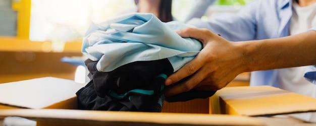 Закройте руку волонтера, упаковывающего коробку из ткани, и сделайте пожертвование другим людям и поделитесь на благотворительность