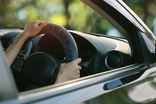 車を運転してステアリングホイール上の女性の手を閉じます。