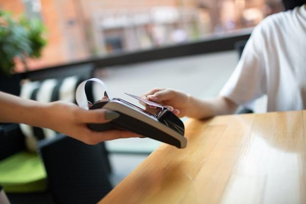 야외 카페에서 신용 카드 비접촉 결제 단말기 계산원으로 여성 지불의 손을 닫습니다