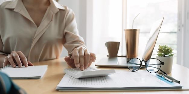 Крупным планом рука женщины, использующей компьютер, рассчитывающего домашние финансы или налоги на машине, женщина управляет домашними семейными расходами с помощью калькулятора, производит оплату на ноутбуке