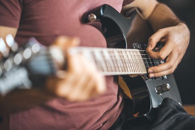 プロの黒いエレキギター、楽器、エンターテインメントで遊んでいる若い男の手をクローズアップ