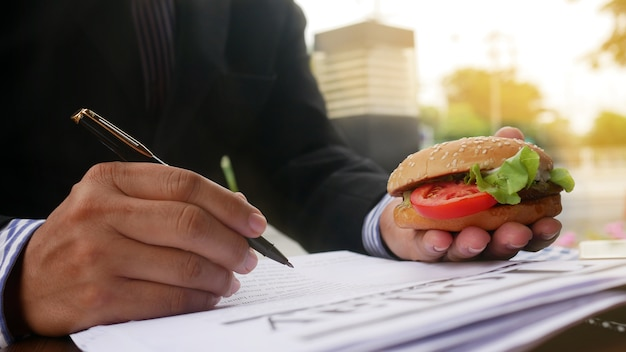 Close up hand of officer working and hold burger and pen outside office.