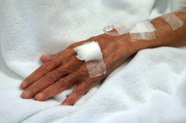 Close up hand of old woman patient saline solution in hospital room